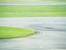 Le bande e le curve della pista di rullaggio e dell'erba verde all'aeroporto Immagine Stock