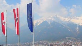 Le bandiere con l'UE, Austria, Tirolo simbolizza l'ondeggiamento in aria, montagne stock footage