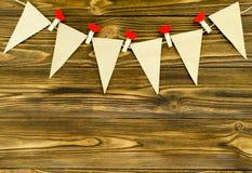 Le bandiere di carta del mestiere con i perni decorativi fanno festa la ghirlanda su woode Fotografia Stock Libera da Diritti