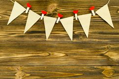 Le bandiere di carta del mestiere con i perni decorativi fanno festa la ghirlanda su woode Immagine Stock