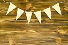 Le bandiere di carta del mestiere fanno festa la ghirlanda su fondo di legno Fotografia Stock