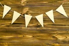 Le bandiere di carta del mestiere fanno festa la ghirlanda su fondo di legno Fotografie Stock Libere da Diritti