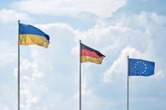 Le bandiere e la bandiera ucraine e tedesche dell'Unione Europea contro lo sfondo delle nuvole Fotografie Stock Libere da Diritti