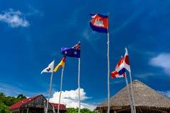 Le bandiere hanno appeso sui bastoni di sostegno per i fagioli di legno con molte nazionalità fotografia stock libera da diritti