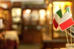 Le bandiere italiane sui bastoni si chiudono su in Di di lusso italiani del ristorante fotografia stock