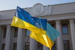 Le bandiere ucraine stanno sviluppando vicino alla costruzione del Parlamento immagini stock