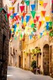 Le bandiere variopinte del partito ondeggiano in un piccolo vicolo Fotografia Stock