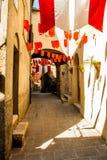 Le bandiere variopinte del partito ondeggiano in un piccolo vicolo Fotografie Stock
