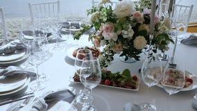 Le banquet avec de grandes tables avec les nappes blanches a assorti des compositions florales délicieuses en plats avec le décor banque de vidéos