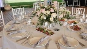 Le banquet avec de grandes tables avec les nappes blanches a assorti les plats délicieux, décor de bougies de compositions floral banque de vidéos