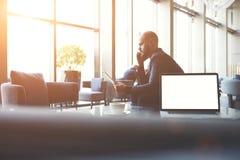 Le banquier masculin s'assied près de la table avec l'ordinateur portable ouvert avec l'écran vide de l'espace de copie pour votr Images stock