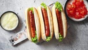 Le barbecue trois a grillé les hot-dogs avec la saucisse placée sur la planche à découper en bois banque de vidéos
