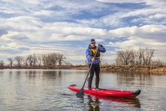 Le barbotage gonflable tiennent le paddleboard image libre de droits