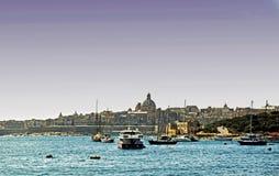 Le barche attraccate in un porto maltese, là sono case, costruzione e una chiesa nei precedenti fotografia stock libera da diritti