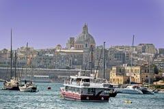 Le barche attraccate in un porto maltese, là sono case, costruzione e una chiesa nei precedenti fotografie stock