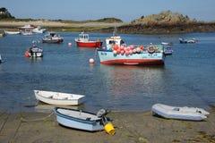 Le barche Colourful hanno attraccato in una baia sabbiosa sulla costa rocciosa Guernsey Fotografia Stock