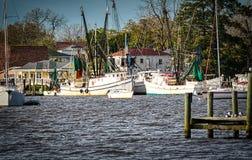Le barche del gamberetto hanno attraccato ad un bacino nel paese basso immagini stock