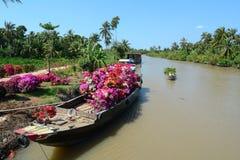 Le barche di legno portano i fiori sul fiume nel delta del Mekong, Vietnam Immagini Stock Libere da Diritti
