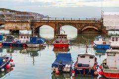 Le barche e le navi hanno attraccato in un piccolo porto, nella pietra del fondo Fotografia Stock Libera da Diritti