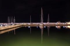 Le barche e le luci al porto hanno riflesso in acqua alla notte fotografia stock libera da diritti