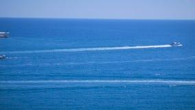 Le barche galleggiano nelle direzioni differenti che lasciano i segni sull'acqua nella bella baia blu del mare Porto di Ibiza Eiv stock footage
