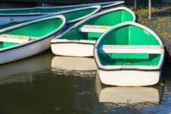 Le barche a remi bianche hanno attraccato al piccolo pilastro con i fiori gialli di caduta Immagine Stock