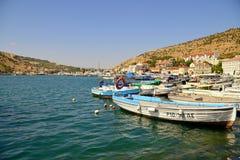 Le barche stanno nella baia contro le colline ed il cielo blu un giorno soleggiato Fotografia Stock Libera da Diritti