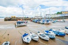 Le barche sulla spiaggia sabbiosa a bassa marea in Tenby abbaiano, Galles Immagine Stock
