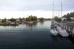 Le barche in villaggio costiero harbor con acqua calma Immagine Stock