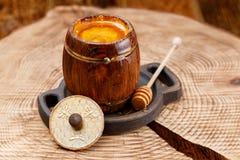 Le baril ouvert avec du miel liquide parfumé et le miel collent dans lui sur une scie en bois photos libres de droits