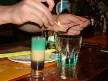 Le barman à la barre met à feu le cocktail avec l'absinthe et le Samb images stock
