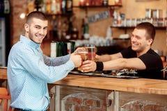 Le barman étire des verres de bière Images libres de droits