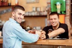 Le barman étire des verres de bière Images stock
