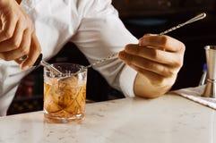 Le barman avec du charme prépare d'une manière élégante un cocktail en versant tout Photographie stock libre de droits