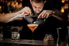 Le barman avec la barbe verse un cocktail d'alcool utilisant la râpe image libre de droits