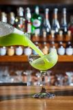 Le barman dans la barre verse un cocktail alcoolique dans un verre avec un courant puissant, non effrayé de se renverser sur la t Images stock