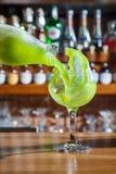 Le barman dans la barre verse un cocktail alcoolique dans un verre avec un courant puissant, non effrayé de se renverser sur la t Image libre de droits