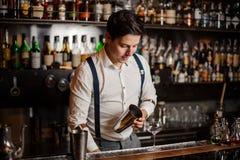 Le barman dans la chemise blanche fait un coctail au compteur de barre photographie stock libre de droits