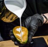 Le barman dans les gants noirs prépare un cappuccino avec le latte un art en avocat Tasse peu commune Café frais et beau avec du  photo libre de droits