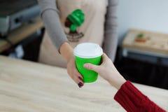 Le barman dans le tablier donne le café chaud dans la tasse de papier à emporter verte au client Le café emportent au magasin de  images stock