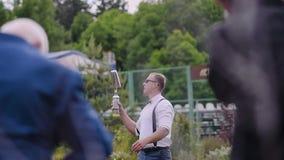 Le barman dans une chemise blanche et des lunettes de soleil est les bouteilles de jonglerie très fraîches devant l'assistance banque de vidéos
