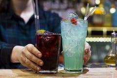Le barman de fille tenant deux boissons sur la barre image libre de droits