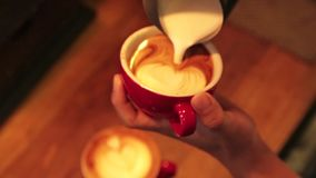 Le barman dessine le lait au-dessus d'un art à café de latte clips vidéos