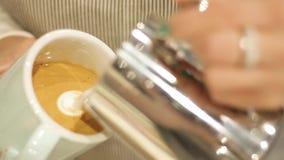 Le barman dessine le lait au-dessus d'un art à café de latte pour le cappuccino banque de vidéos