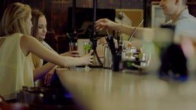 Le barman donne des cocktails à de jolies filles clips vidéos