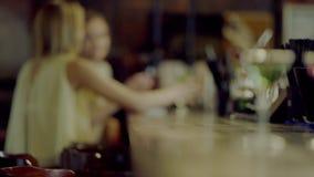 Le barman donne des cocktails à de jolies filles banque de vidéos