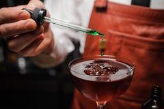 Le barman expert fait le cocktail finissant en laissant tomber amer vert image libre de droits