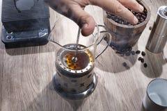Le barman faisant le français pressent avec un seau de grains de café images libres de droits