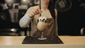 Le barman femelle met une paille noire dans un verre de tulipe avec une boisson de café dans lui Un plan rapproch? banque de vidéos