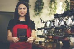 Le barman femelle mignon professionnel a fait l'americano utilisant la machine de café fonctionnant dans le cafétéria Photo libre de droits